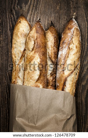 Four baguette bread loaves in paper bag on wooden background - stock photo