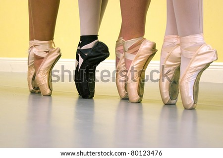 Four ballerinas are standing on their toes, on pointe, wearing ballet shoes of various types during dance class. - stock photo