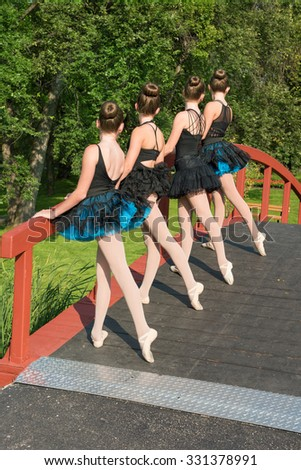 Four ballerinas on a bridge in the park practicing a routine