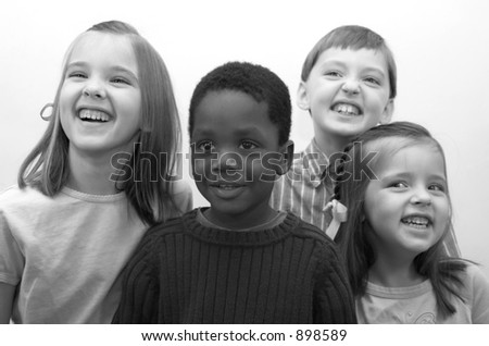 Four beautiful children smiling for the camera. - stock photo