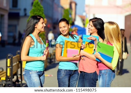 four beautiful college girls talking on the street - stock photo