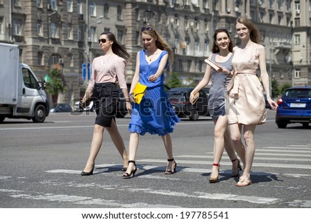 Four beautiful fashion women walking on the street in Moscow city - stock photo