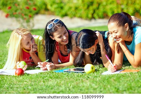 four beautiful girl having fun outdoors on green lawn - stock photo