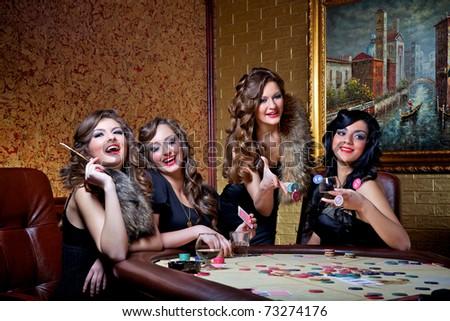 Four beautiful girls play poker - stock photo