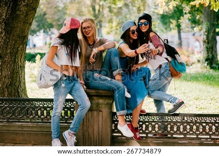 four beautiful girls sitting on the fence - stock photo
