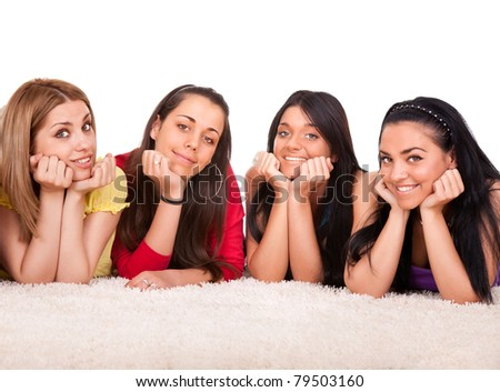 four beautiful, happy, smiling young girls laying on white floor, isolated on white background - stock photo