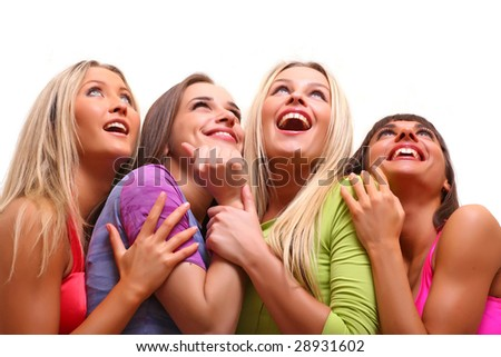 Four beautiful happy young women with a smile in bright multi-coloured clothes look upwards, isolated on a white background - stock photo
