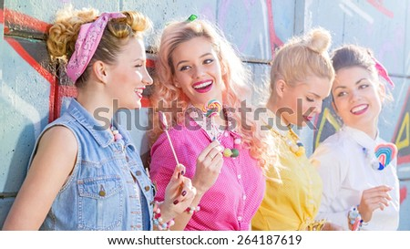 Four beautiful Pin Up girls posing against the graphite wall with lollipop. Retro style. Lens Flare. Focus on one person. - stock photo