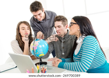 Four beautiful students of Geography learning with globe and laptop.