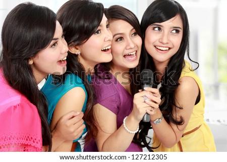 Four beautiful stylish woman singing karaoke together - stock photo