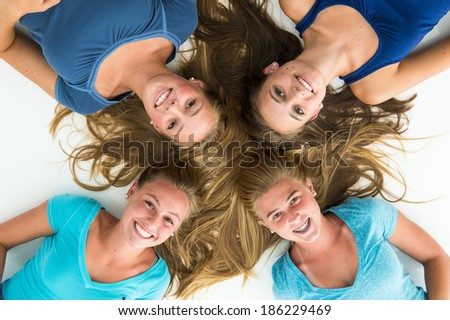 Four beautiful teen girls, smiling, overhead view. Wearing casual blue clothing.
