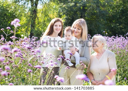 Four beautiful women of one family in a summer garden - stock photo