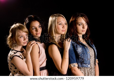 Four beautiful young female friends posing behind each other in a row against a dark background - stock photo