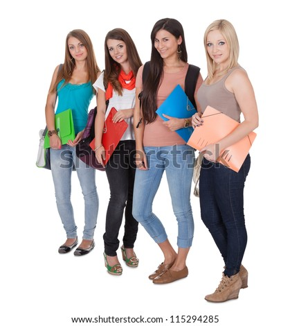 Four beautiful young female students standing in a receding row with folders of notes under their arms isolated on white - stock photo