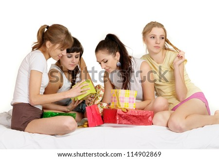 Four beautiful young girl with gifts on bed - stock photo