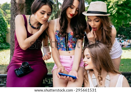 four beautiful young girls looking at the photos on a smartphone in the park
