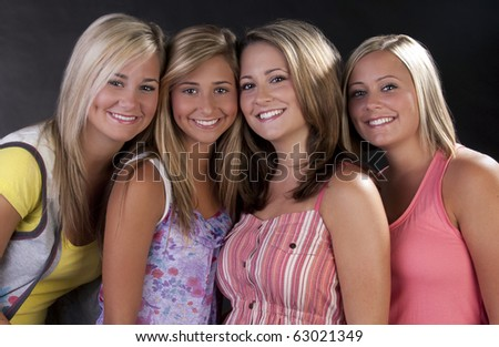 four beautiful young women posing together.