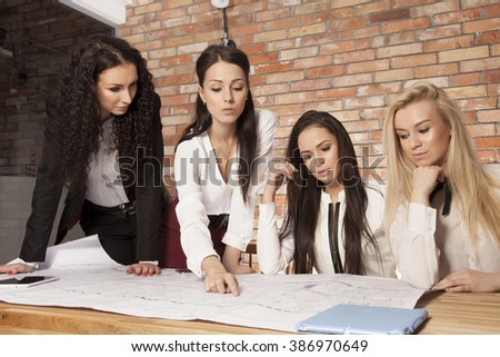 Four beauty young adult businesswomen at office working with laptop - stock photo