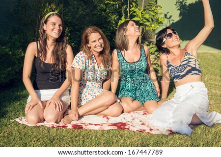 Four best girl friends laughing in the garden - stock photo