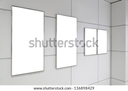 Four big vertical / portrait orientation blank billboard on white wall in public open space