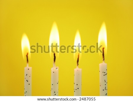 Four birthday candles on a yellow background. - stock photo