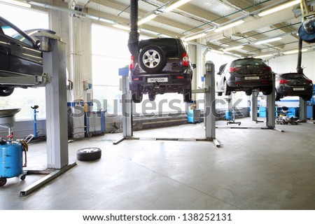 Four black cars on lifts in small service station. Cars prepared to diagnosis and repair. - stock photo
