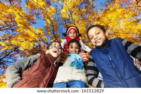Four black kids, boys and girl, siblings, brothers and sister, smiling, laughing and looking down standing in autumn park - stock photo