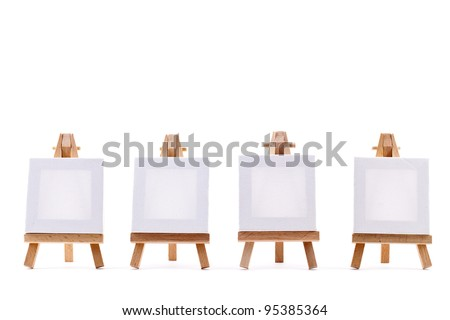 Four blank canvases on easels