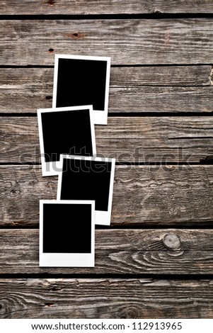 Four blank instant photo frames on old wooden background. - stock photo