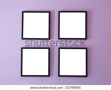 Four blank picture/photo frames on wall - stock photo