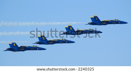 Four Blue Angels Navy Flight Demonstration Team planes flying horizontally in a tight formation during Fleet Week 2006 air show in San Francisco - pilots in yellow helmets clearly visible.