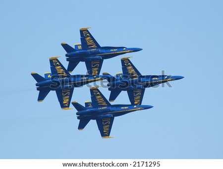 Four Blue Angels planes flying in a tight diamond formation.