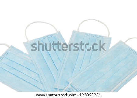 Four blue medical masks on a white background - stock photo