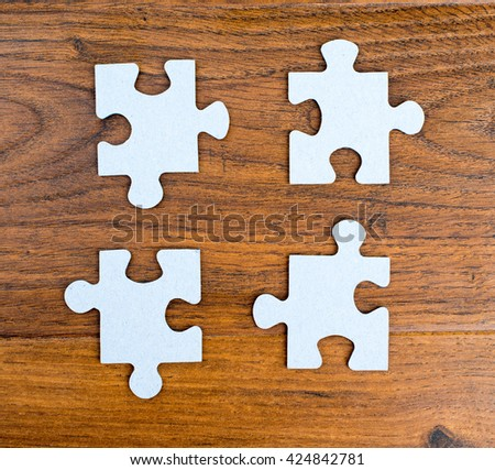 Four blue pieces of puzzle on wooden background - stock photo