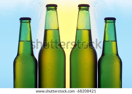 Four bottles of beer with cold droplets
