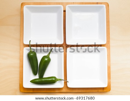 Four bowls of which one contains chili peppers - stock photo