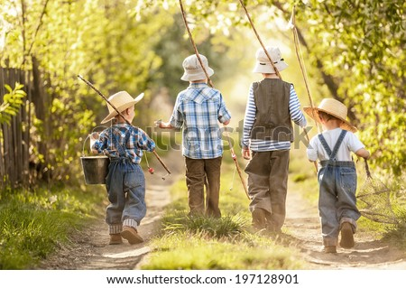 Four boys with fishing rods go on a fishing trip on the narrow rural road in sunny summer day - stock photo