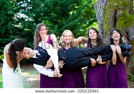 Four bridesmaids having fun, carrying groom in their arms sideways - stock photo