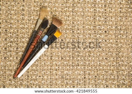 Four brushes at a brown background