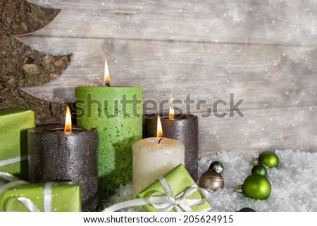 Four burning advent candles in green and brown on wooden background. - stock photo