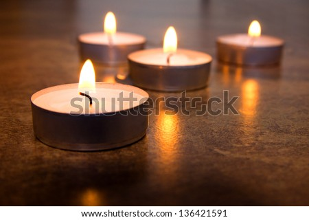 Four burning candles on marble surface (background) with reflection. Close up scene, copy space. Concept of memory, meditation, relaxation. - stock photo