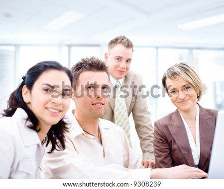 Four business colleagues working together on laptop computer in office, looking at camera, smiling. Focus placed on sitting man in middle.
