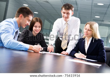 Four business colleagues working together, smiling - stock photo