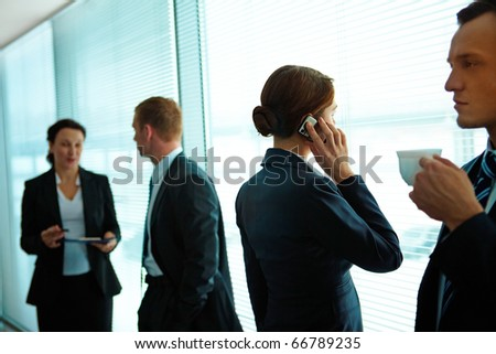 Four business partners interacting in office - stock photo
