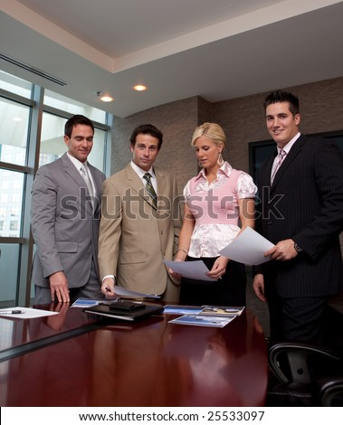 Four business people at a conference table over a project - stock photo