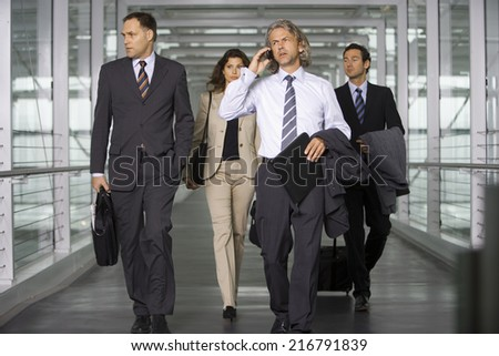 Four business people at the airport. - stock photo