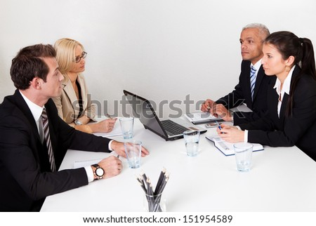 Four business people discussing in the meeting - stock photo