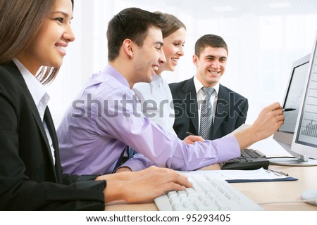 Four business people during a meeting sitting around a table - stock photo