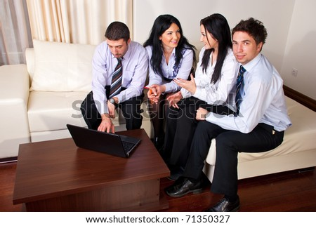 Four business people having a discussion,using laptop and sitting all  on a beige couch in a workplace - stock photo