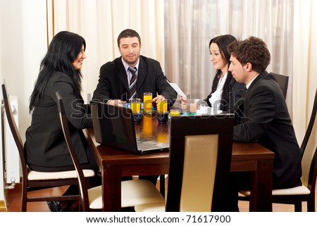 Four business people having a meeting  and standing at table and discussing together - stock photo